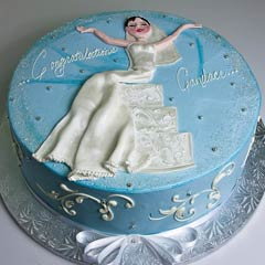 Round blue bridal shower cake decorate with white swirls and a bride wearing a white bridal gown cake design