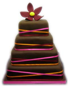 Elegant brown four tier square wedding cake decorated with thin pink, orange and burgundy satin ribbons