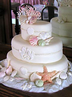Three tier oval white cake decorated with sea horses, pink sea coral and colourful seashells