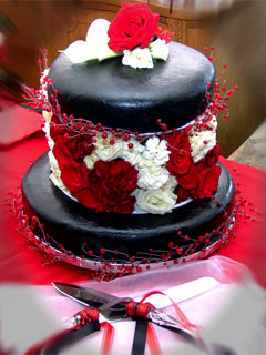 Two tier white, red and black fondant wedding cake