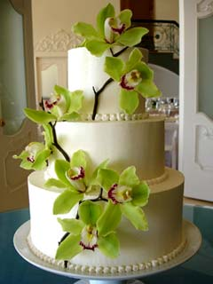 Round three tier wedding cake covered in royal icing and decorated with green Cymbidium Orchids