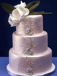 Light metallic pink fondant frosted wedding cake decorated with diamontee's brooches and a lovely white flower wedding cake topper