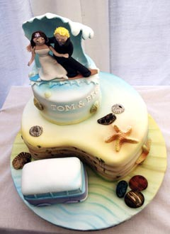 two tier beach theme wedding cake with caricatures of the bride and groom
