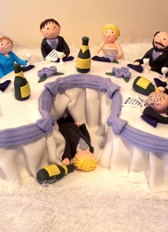 Humorous novelty wedding cake with caricatures of the bride and groom and the bridal party