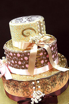 three tier round wedding cake is covered and decorated with gold scrollwork and tied with pink, gold and bronze ribbons