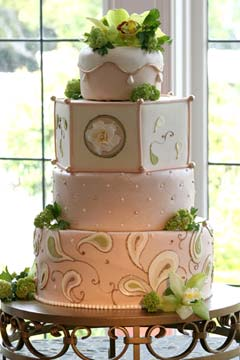 Elegant beige and ivory four tier wedding cake decorated with hand painted paisley patterns and fresh green Cymbidium Orchids