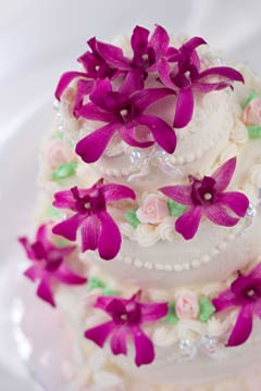 Three tier white fondant wedding cake decorated with pink tropical flowers