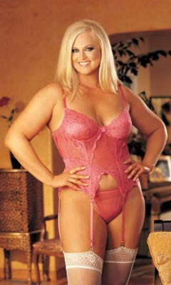 Blonde plus size model wearing pink stretch lace bustier in plus size. Underwired cups, adjustable straps, garters and a sexy strappy back