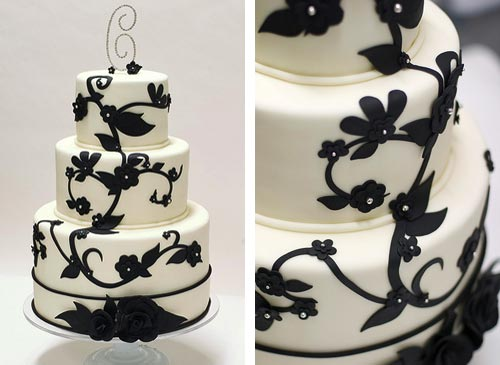 Round three tier white retro wedding cake decorated with black fondant swirls, flowers and branches. A closeup of the hand crafted fondant flowers with small silver sugar balls in the centre