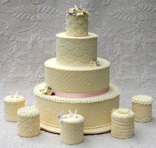 Four tier intricately designed ivory victorian style wedding cake with mini wedding cakes to match