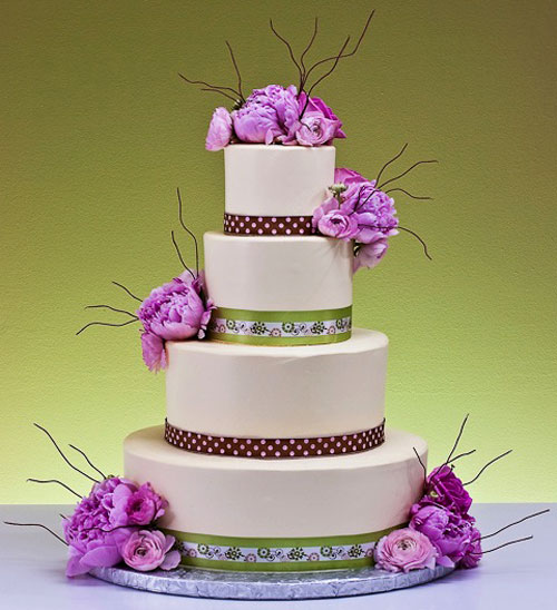 four tier floral wedding cake decorated with flowers, covered in ivory frosting and decorated with fresh pink peonies