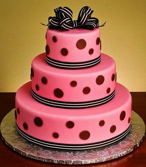 Pink two tier fondant wedding cake covered with black polka dots