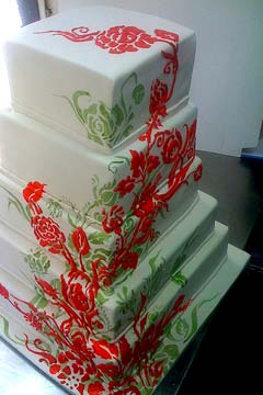 Five tier white, red and green wedding cake decorated with red and green floral art work