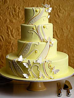 Very arty, four tier, yellow retro wedding cake, decorated with swirls and pattens from the 1940's