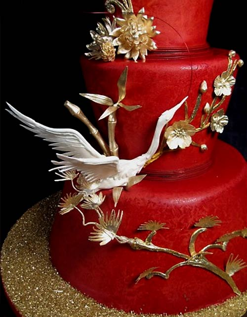 Unusual three tier red wedding asian cake decorated with gold cherry blossoms