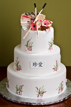 Round three tier white Asian style wedding cake with Asian fan and Chinese chop sticks wedding cake topper