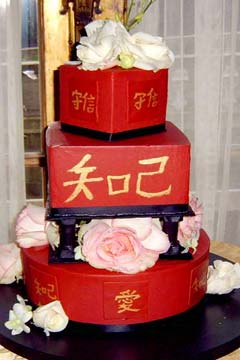 Square and round three tier red Chinese wedding cake decorated with gold Asian marriage symbols