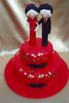 Chinese red wedding cake decorated with gold leaf flowers and black intricate scroll work