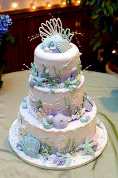 Three tier white wedding cake decorated with purple, blue and green seashells