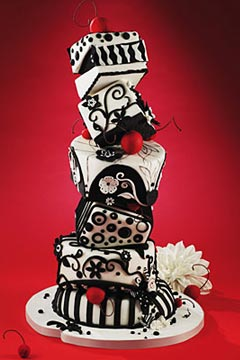 Black and white, whimsical five tier topsy turvy wedding cake decorated with black and white scrolls, patterns and shapes
