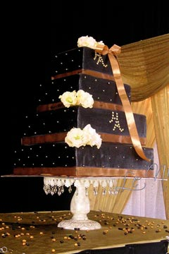 Four tier black and brown square wedding cake decorated with white fresh roses