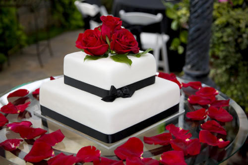 Black and white wedding cakes gallery traditional square two tiered white wedding cake with black satin ribbon decorated with fresh red roses junglespirit Image collections