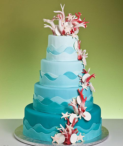 Unique, four tier aqua blue beach theme wedding cake. Decorated with