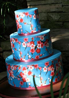 Three tier blue buttercream wedding cake decorated with hand painted white, pink and red cherry blossoms