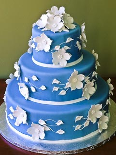 Round three tier bright blue fondant wedding cake, decorated with beautifully made white sugar paste flowers