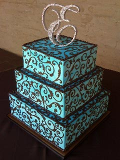 Three tier square blue and brown wedding cake, decorated with intricate brown brocade scroll patterns