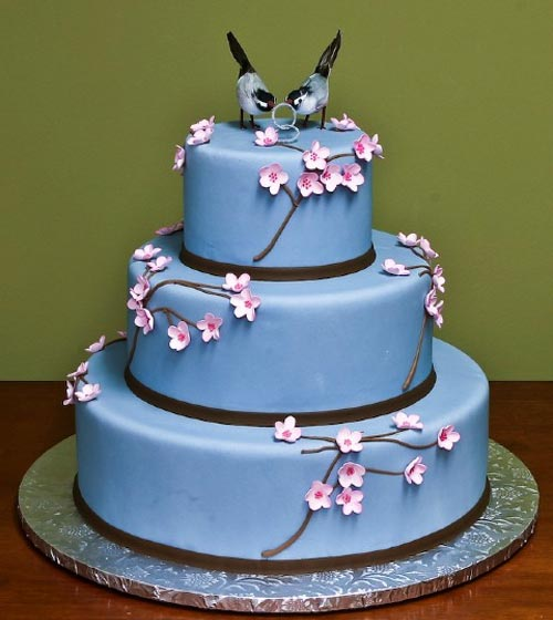 Charming three tier blue cherry blossom wedding cake, decorated with handmade pastel pink cherry blossom flowers