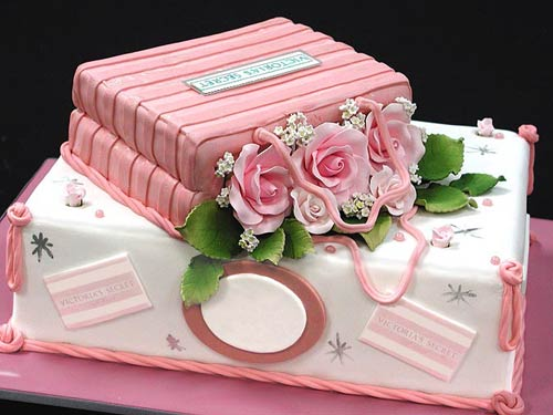 Adorable, two tier, pink suitcase bridal shower cake, decorated with pink sugar paste flowers and leaves
