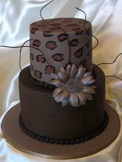 Unusual round two tier brown and leopard print wedding cake decorated with a faux brown silk flower