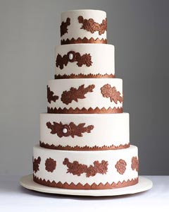 Exotic five tier white wedding cake decorated with bronze brown medallions