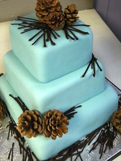 Two tier blue fondant wedding cake with brown pine cones