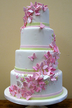 White Bridesmaid Dress on Four Tier White Round Wedding Cake With Handmade Pink Butterflies As