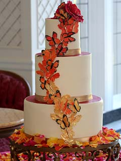 Round three tier ivory and fuchsia coloured wedding cake decorated with vibrant orange and gold butterflies