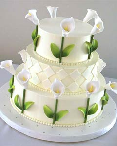 Modern three tier white buttercream wedding cake, beautifully decorated with handmade sugar Calla Lillies