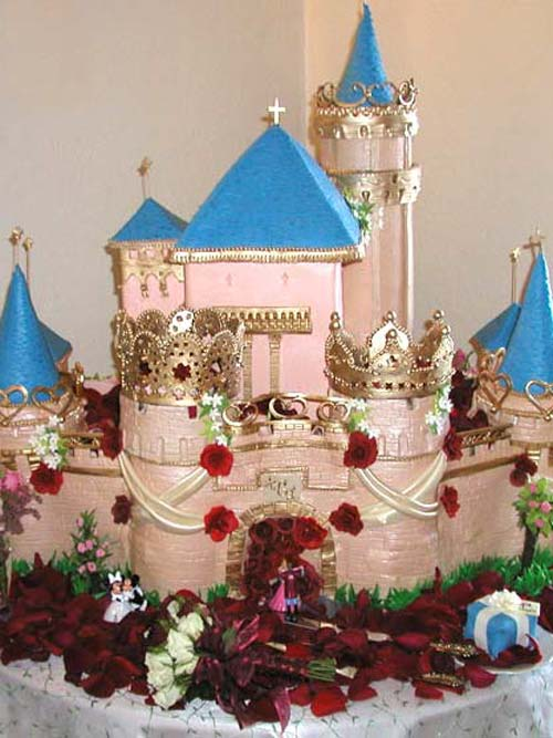 princess wedding cakes. castle wedding cake design for a fairy tale theme. hand painted blue and apricot to look real castle. beautifully decorated with gold crowns princess cakes