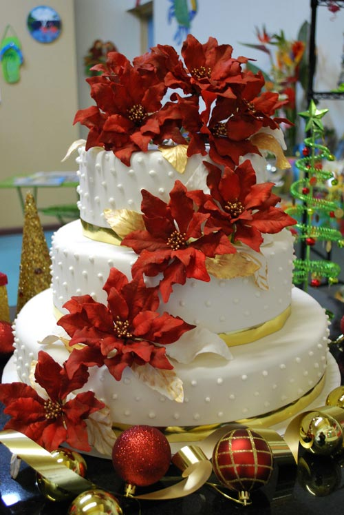 Three tier white, red and gold Christmas wedding cake, decorated with cascading red Christmas flowers and red and gold Christmas decoration balls