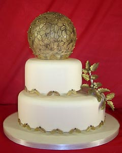 Round, three tier ivory and gold wedding cake, decorated with gold Christmassy accents