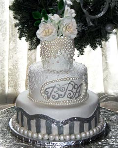 Three tier Christmas theme white and silver wedding cake, decorated with large white pearls and white rose wedding cake topper