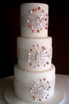 Contemporary three tier white wedding cake embellished with pink, orange and white pearl edible decorations