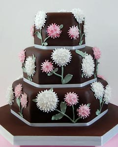 Contempory, three tier chocolate hexagon wedding cake, decorated with unusual white and pink buttercream flowers