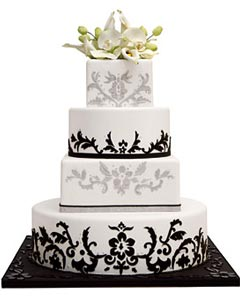 Four tier, white round and square contemporary wedding cake, decorated with black and silver brocade patterns