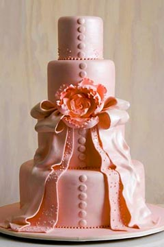 Romantic pink contemporary design wedding cake. Decorated to look like the brides wedding dress, covered with pink drapes of fondant