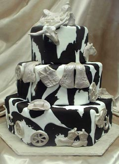 Three tier brown and white western style hexagon wedding cake, decorated with fondant cow hide