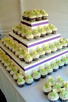 Four tiered white and green mini wedding cakes