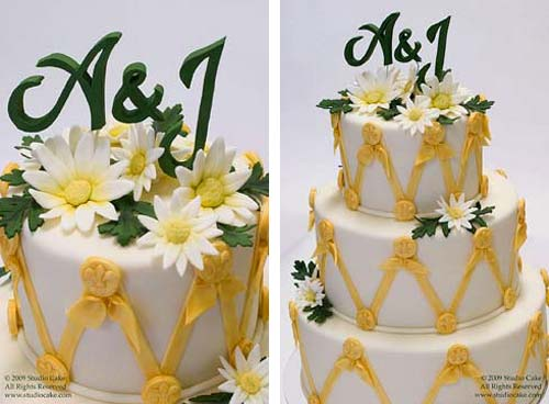 Three tier white and yellow designer wedding cake decorated with white and yellow fondant daisies