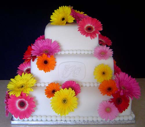 wedding cake decorated with pink yellow orange and red gerbera daisies